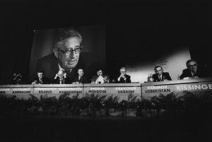 reunión WEF con Kissinger en segundo plano en pantalla gigante