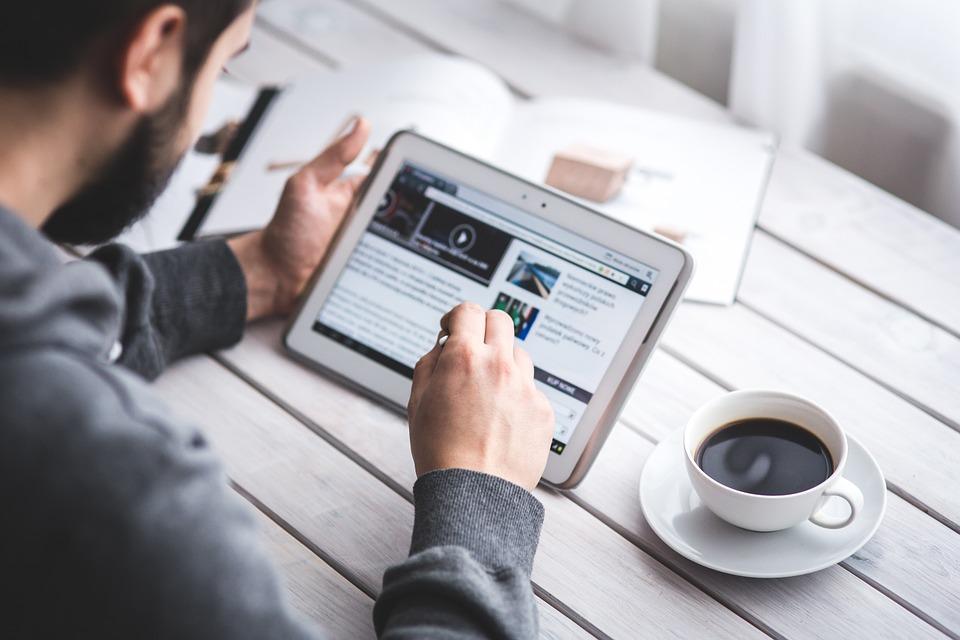 hombre leyendo tablet con café