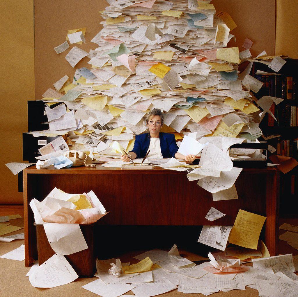 montaña de papeles sepulta oficinista